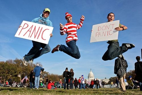 Three people jumping in the air holding signs that say panic and don't panic